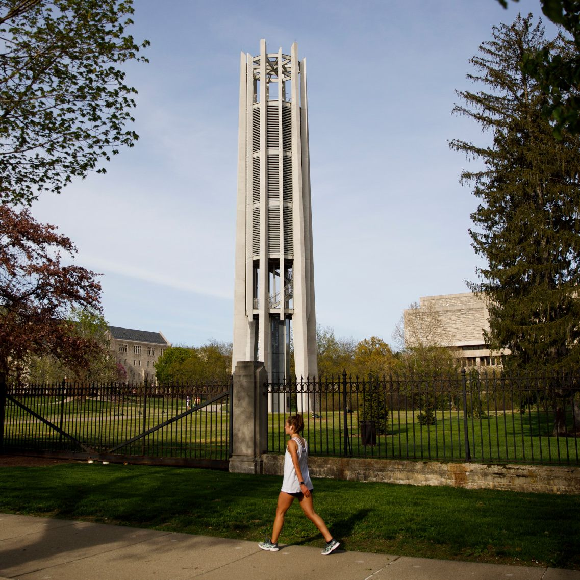 A woman walks along a path near the Metz Grand Carillon.