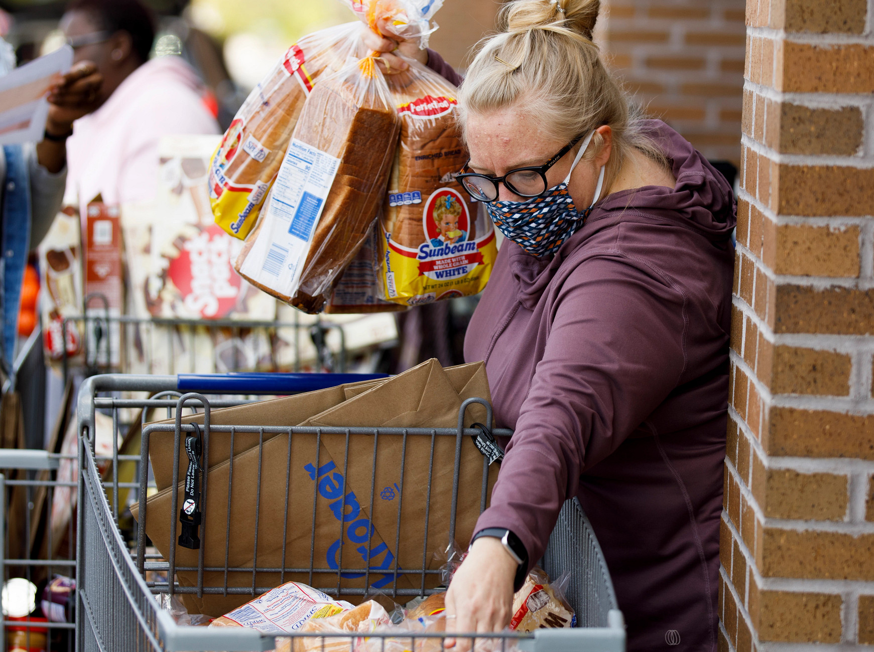 A masked woman takes bread from a cart