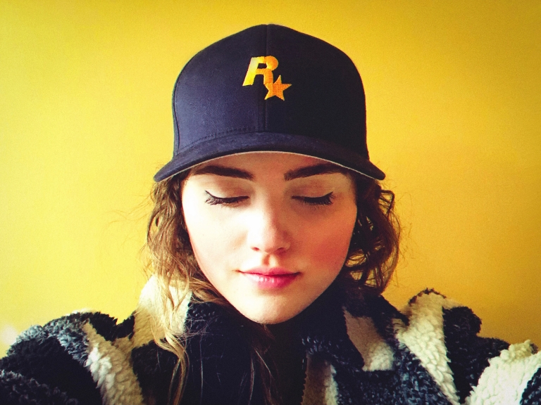 woman wears a blue hat with a yellow Rockstar Games logo