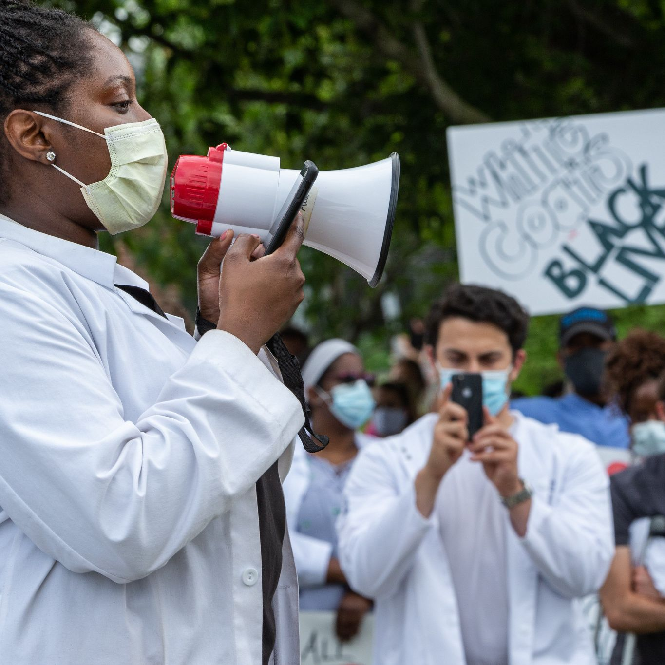 A woman in a white coat and mask speaks into a megaphone, a sign says 'white coats black lives'