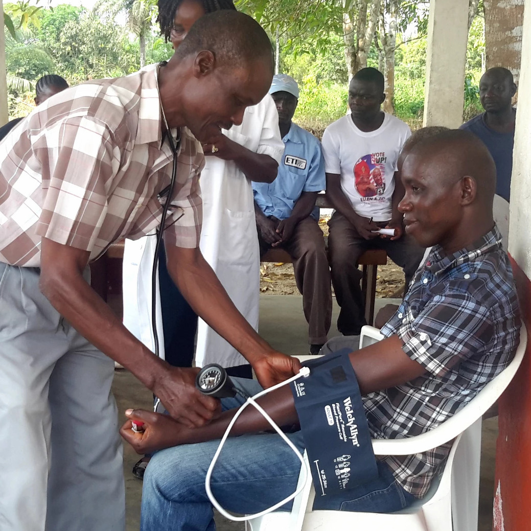 A Liberian man learns to take another man's blood pressure