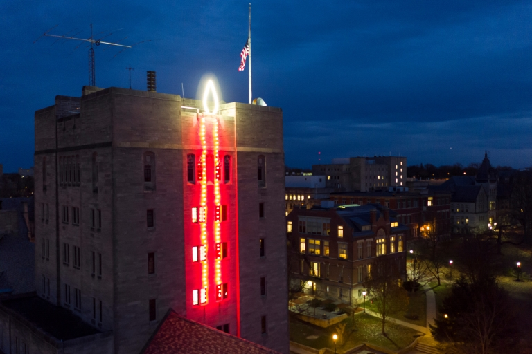Red lights form a giant candle on the side of IU's union building