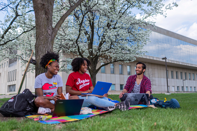 Students sit under a tree with their laptops on the IUPUI campus