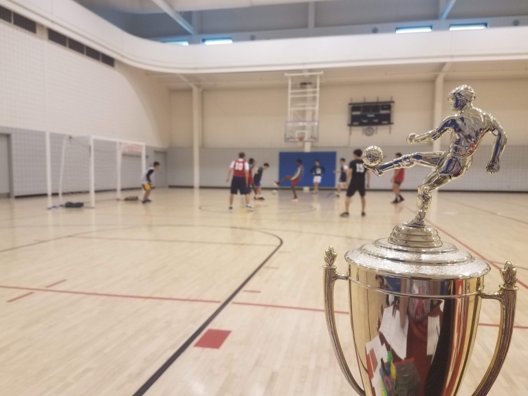 A trophy with people playing soccer behind it