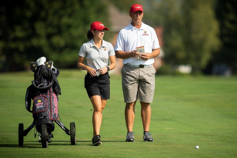 Male golf coach talks with a female golfer during a match