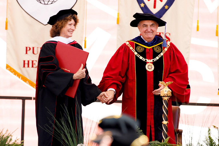 Michael A. McRobbie and Laurie Burns McRobbie on stage to receive honorary degrees.