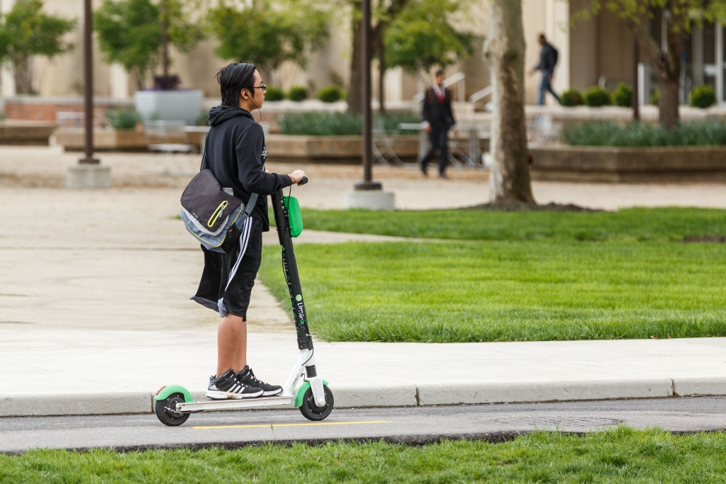 A student on a scooter on campus