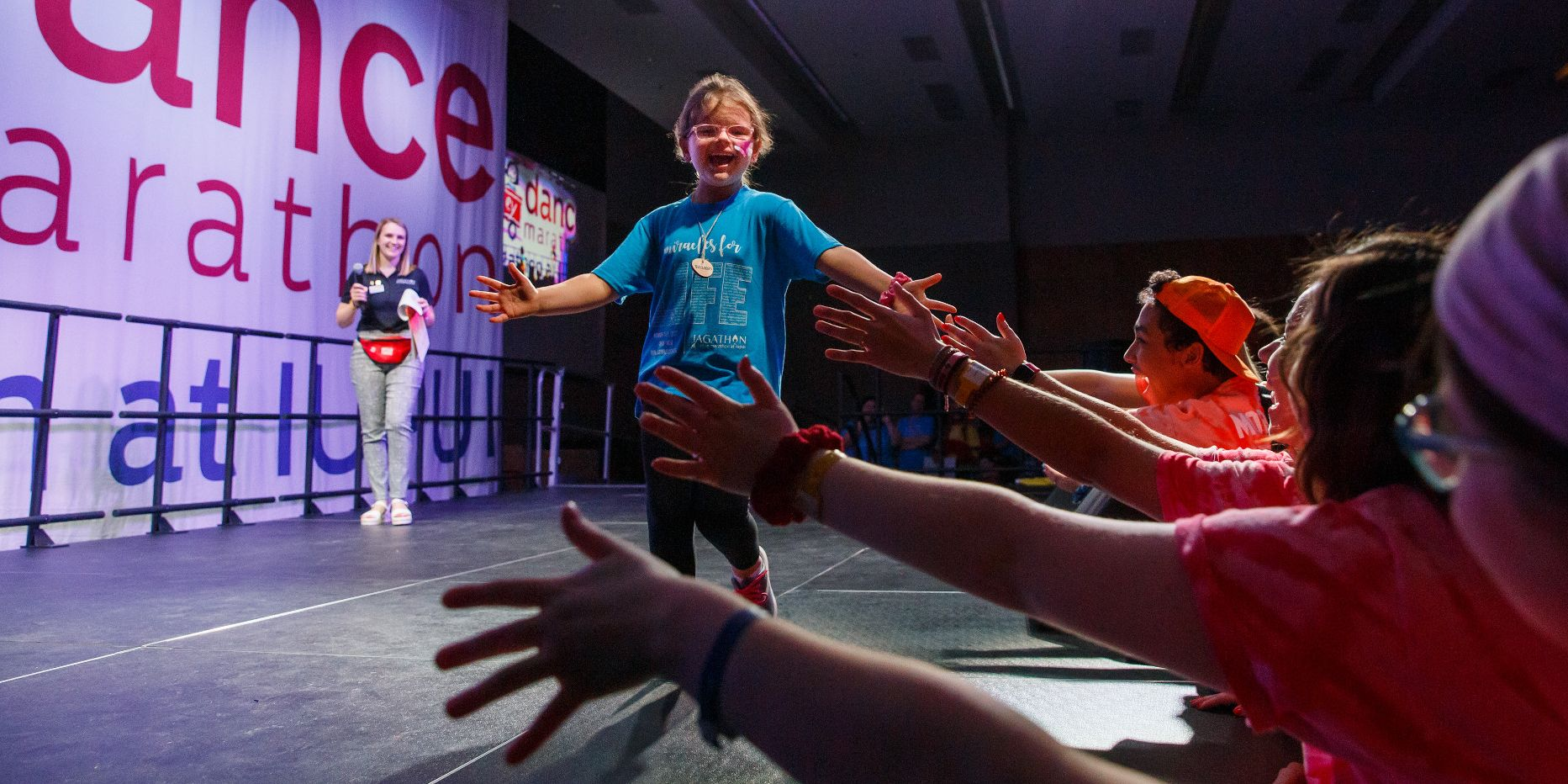 A kid runs across the stage and high-fives people in the crowd at Jagathon