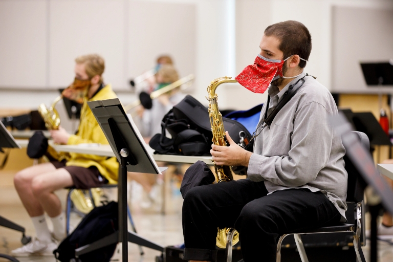 Student wears special mask while playing saxophone