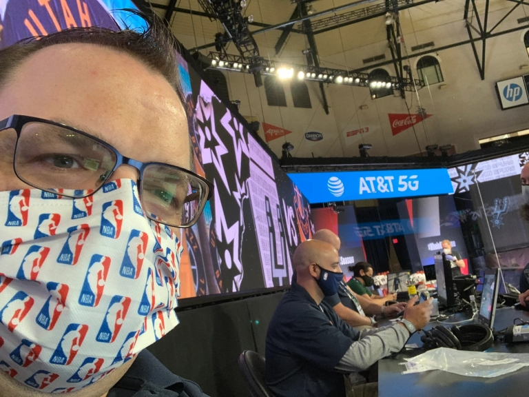 a man wearing a mask is sitting at the scorer's table at an NBA game