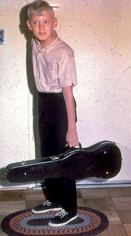 Young Glenn Gass stands near a closed door holding a violin case