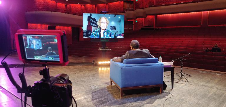 Man interviews woman through flat-screen tv