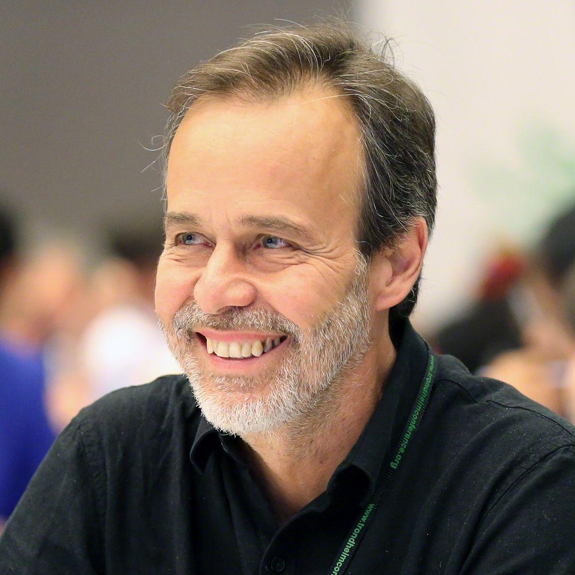 Eduardo S. Brondizio smiles while sitting at a table.