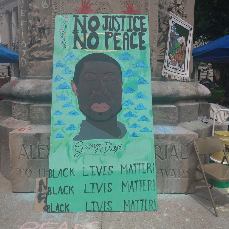 A sign with a drawing of George Floyd reads 'No Justice, No Peace' and 'Black Lives Matter'