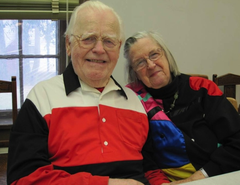 An older man and woman sit closely together to pose for a picture.
