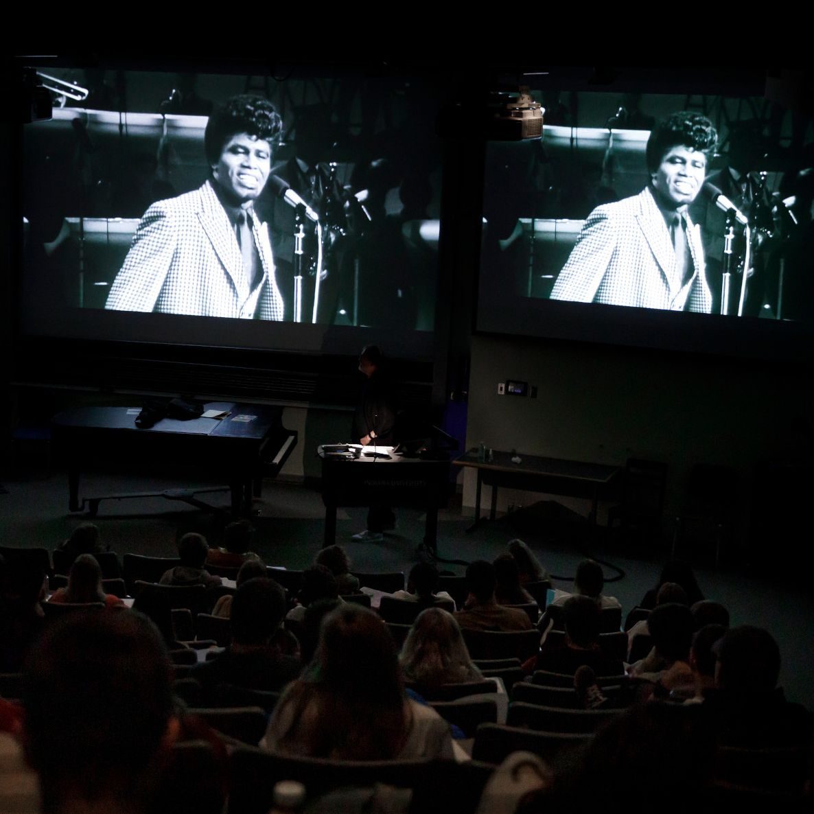 Students watch an archival video clip on the screen of a darkened lecture hall