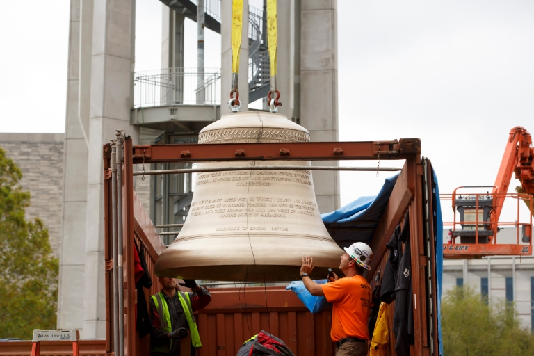 A worker attaches a bell to a crane for placement