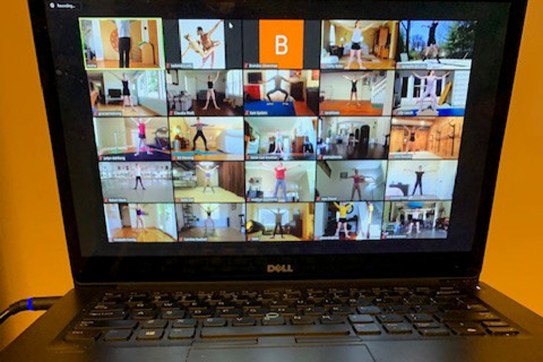 A laptop with a Zoom meeting displayed showing several ballet dancers during a technique class.