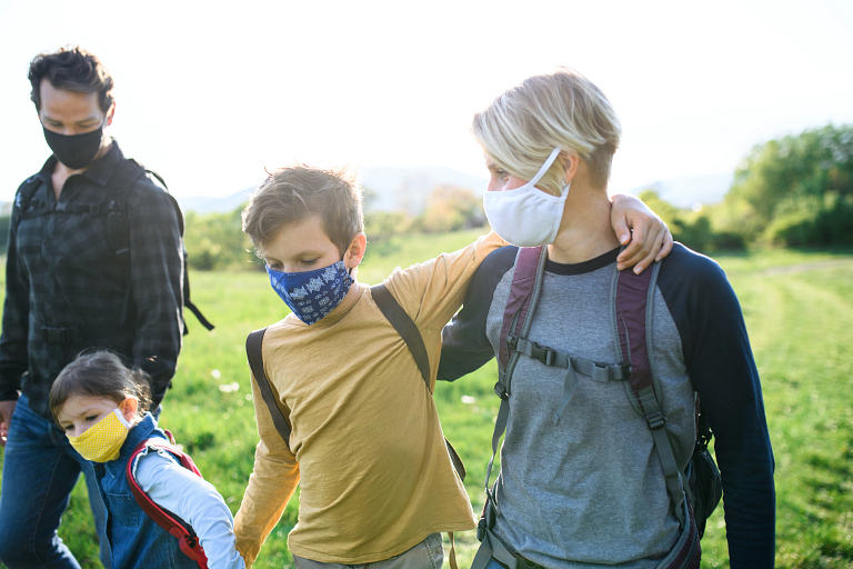 A family wearing face masks takes a walk in the countryside