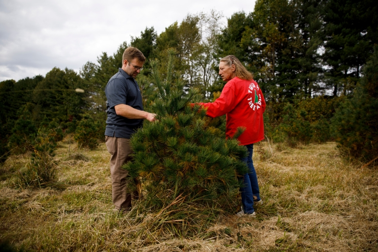 James Farmer and Jean Hopwood standing near an evergreen tree