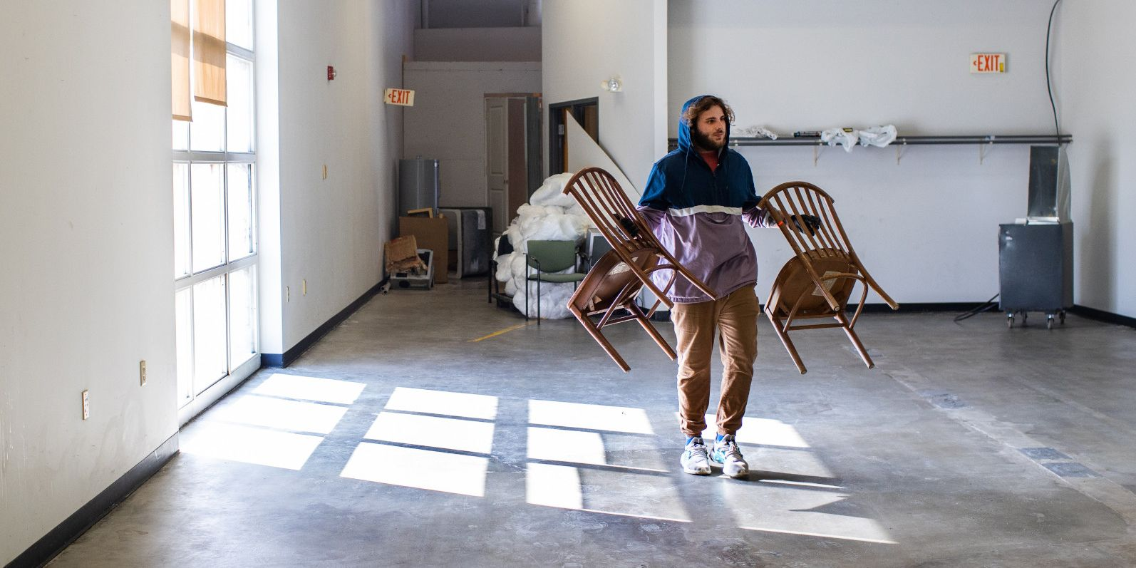 A mover carries two chairs across a mostly empty room