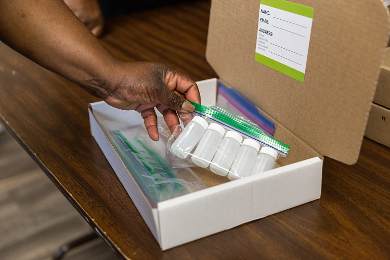 A closeup of a hand placing small plastic bottles into a box with an address label inside the lid