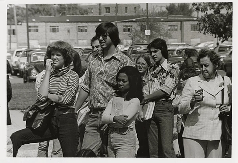 a group of students stand around outside in 1977