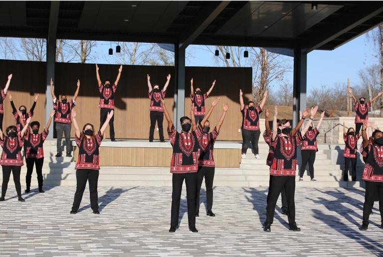 Members of the African American Choral Ensemble rehearse outdoors