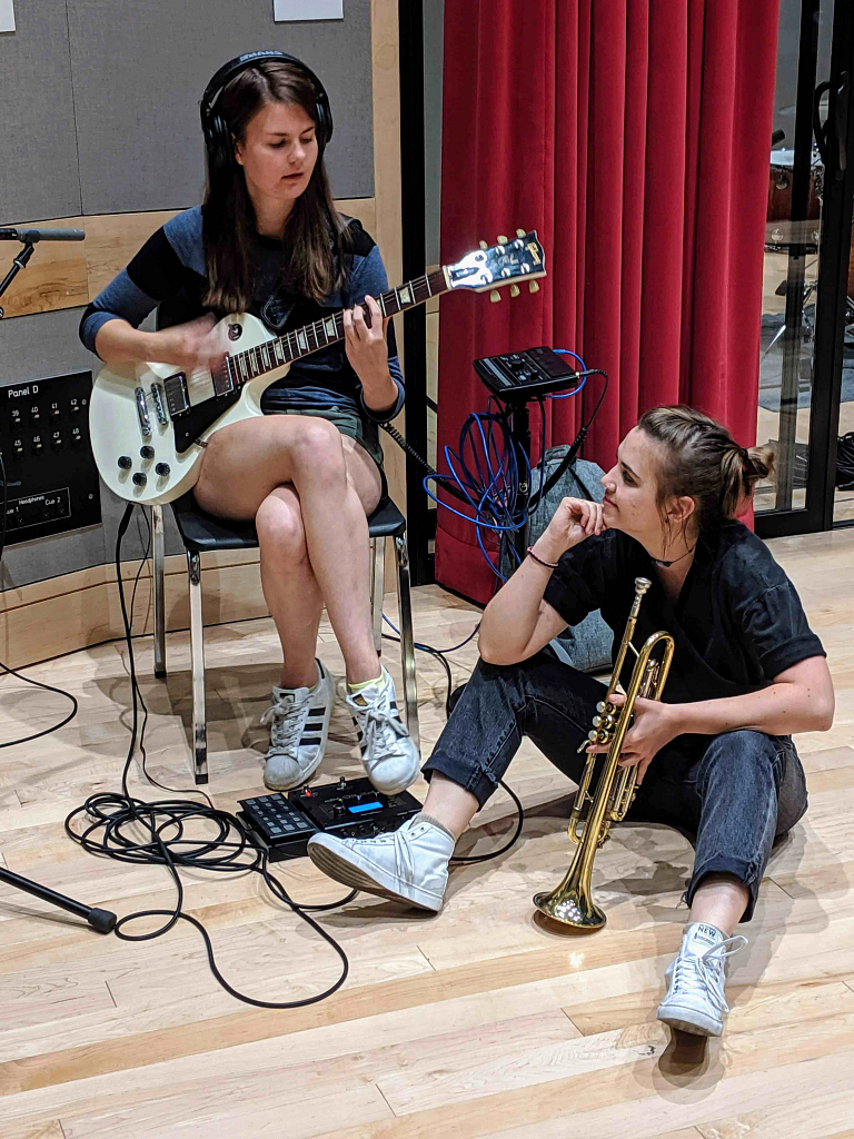 Woman plays guitar next to woman holding trumpet