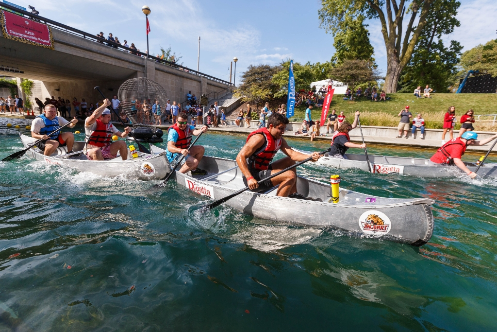 Three teams are racing in canoes on the canal