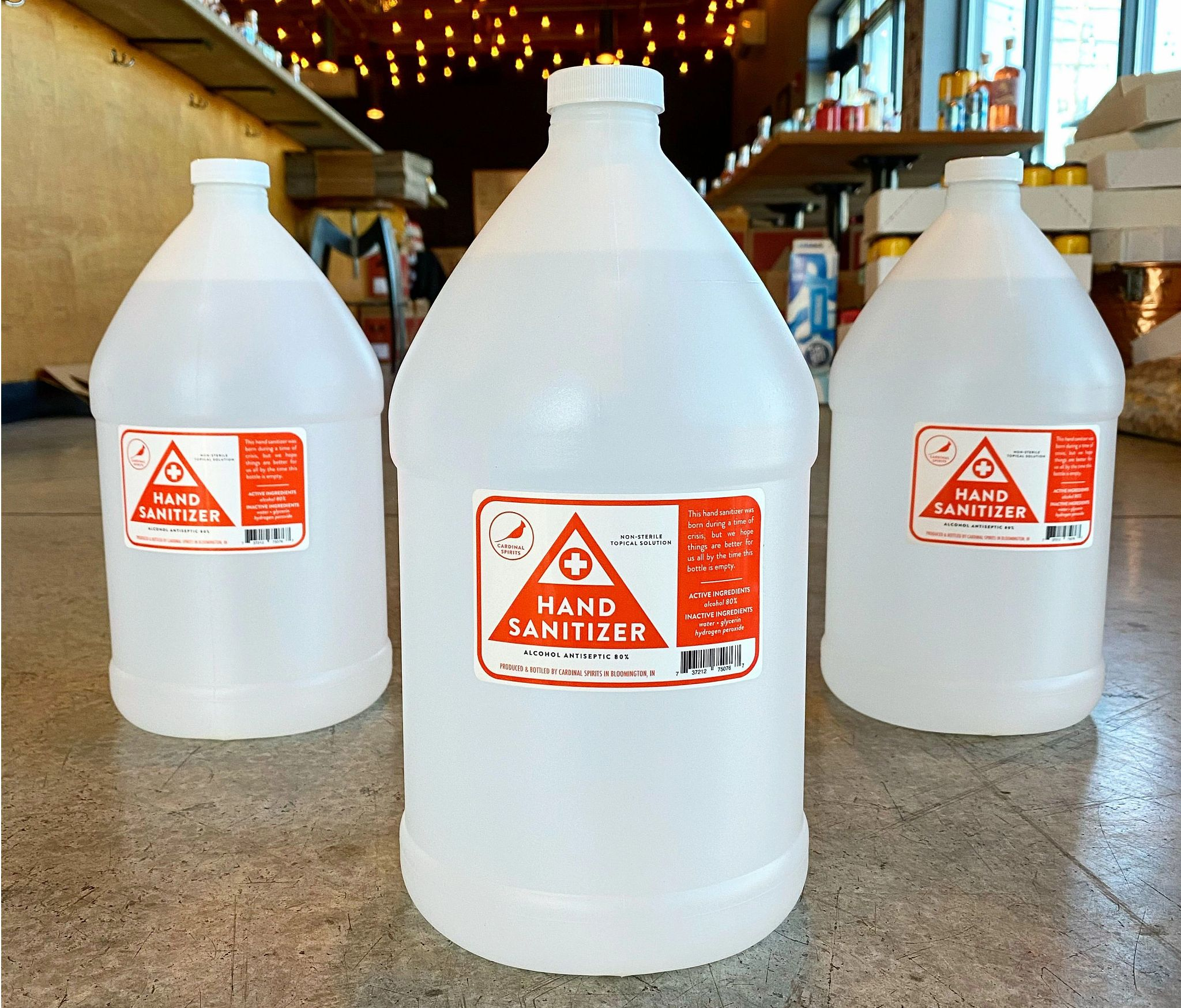 Three clear gallon jugs with red hand sanitizer labels sit on the floor.