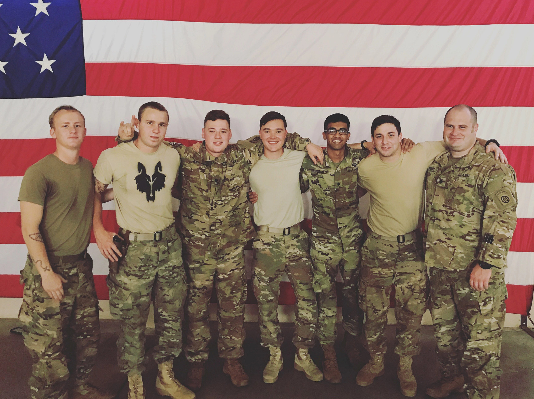 Seven U.S. Army soldiers stand in front of a large American flag