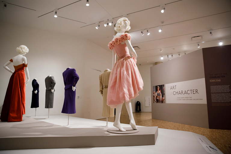 A pink silk organza dress on a mannequin in the center of an exhibition of other dresses