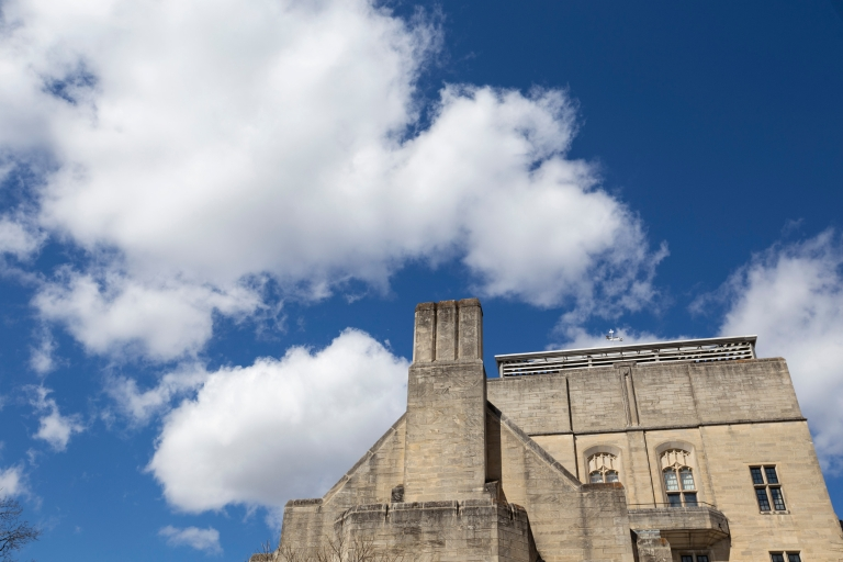 A blue sky with puffy white clouds and a limestone building in the foreground.