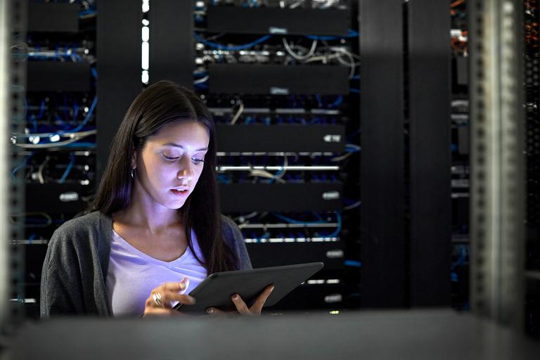 Engineer using a digital tablet in a server room