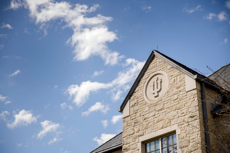 A limestone trident adorns the side of the Hutton Honors College on a spring day