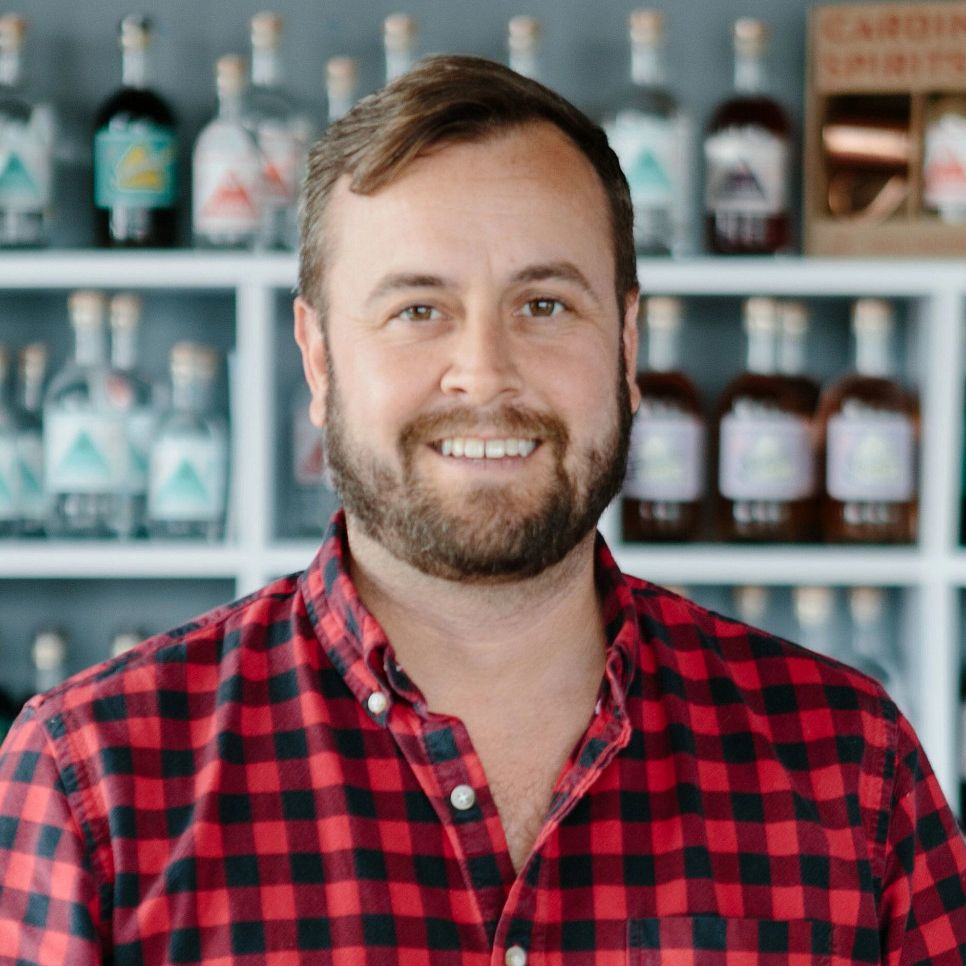 Adam Quirk wears a flannel shirt while sitting in front of bottles of distilled spirits.