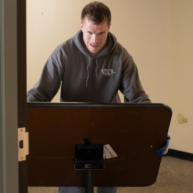 A mover in a gray hoodie sets up a table