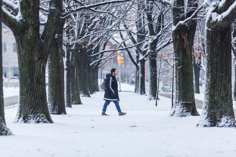 A student walking through the snow on campus