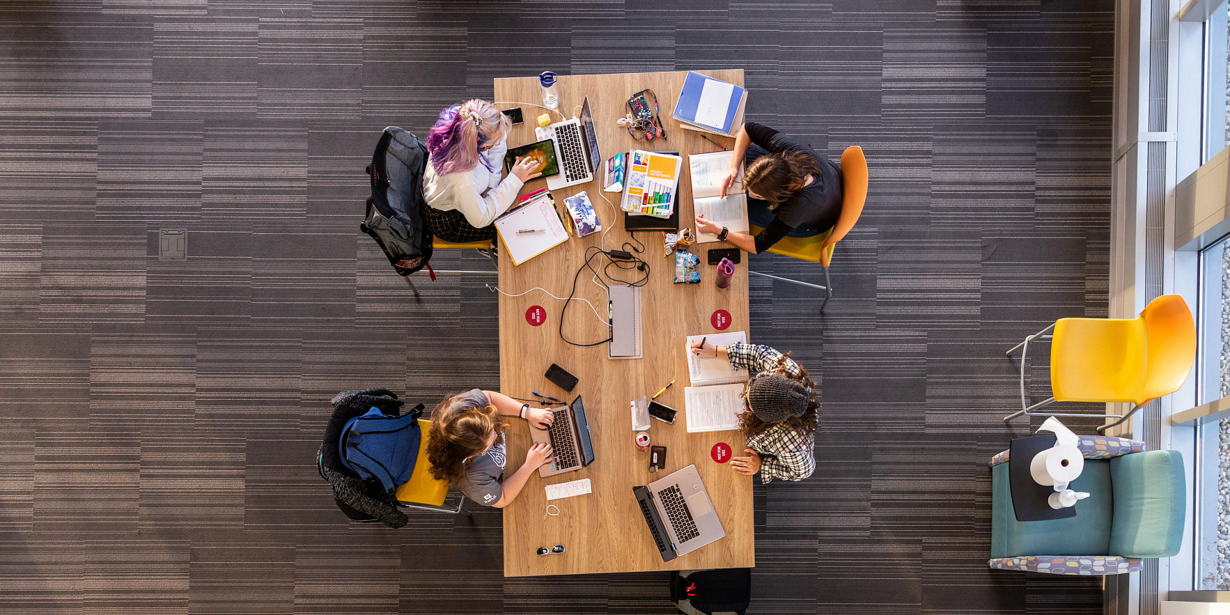 an overhead view of four students working at a table
