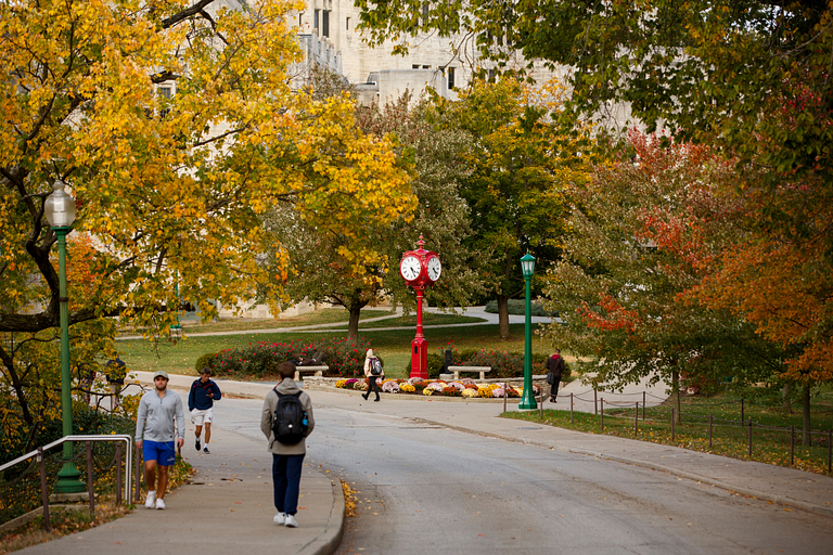 Students walk near a red clock on the IU Bloomington campus, surrounded by fall colors