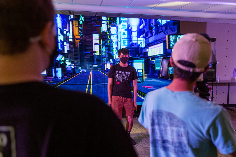 A student stands in front of a virtual world during filming of a commercial