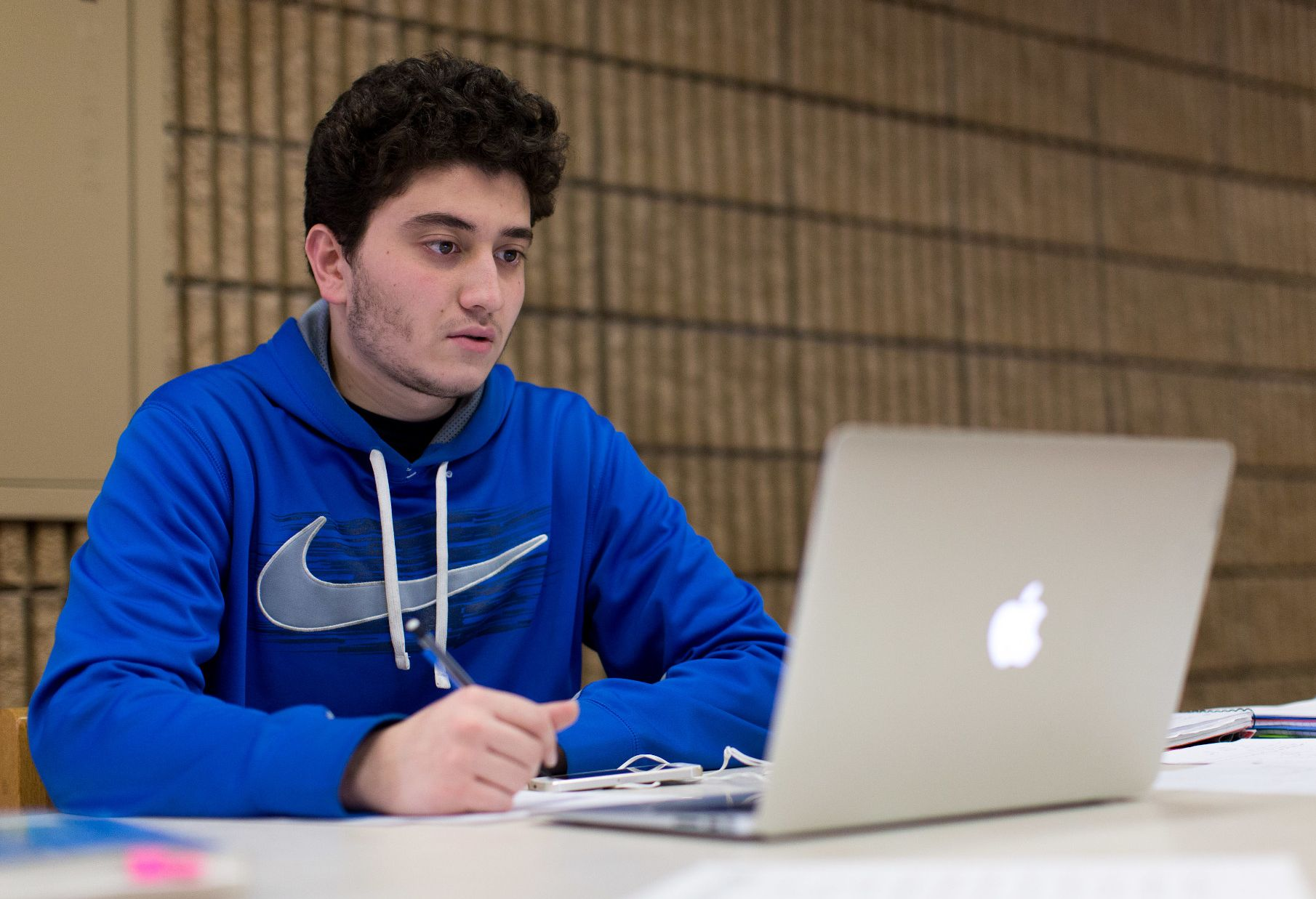 A male student in a blue sweatshirt looks at his laptop