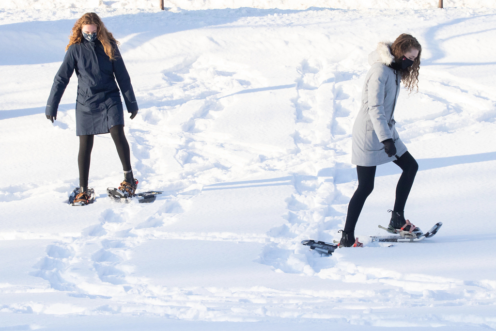 Two snowshoers practice in a snow-covered Dunn Meadow