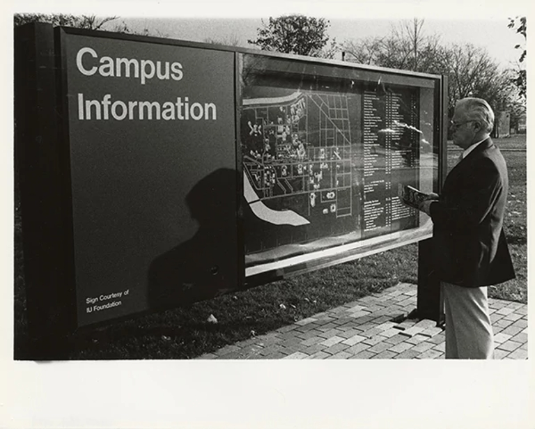 A man stands at an older campus information and map board.