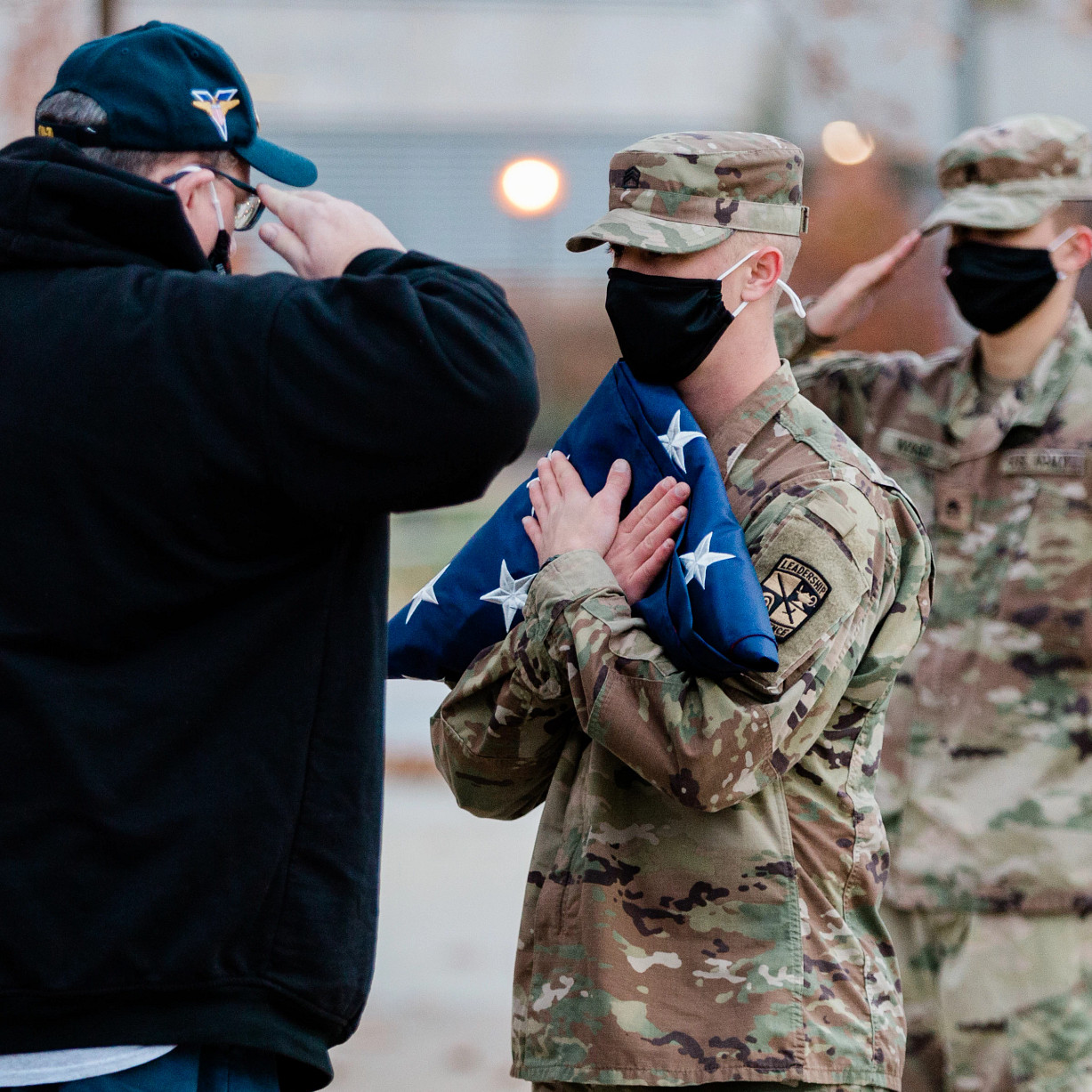 A man salutes a soldier holding a flag