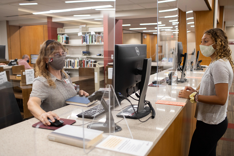 A masked library worker helps a masked student at IU Bloomington's Wells Library