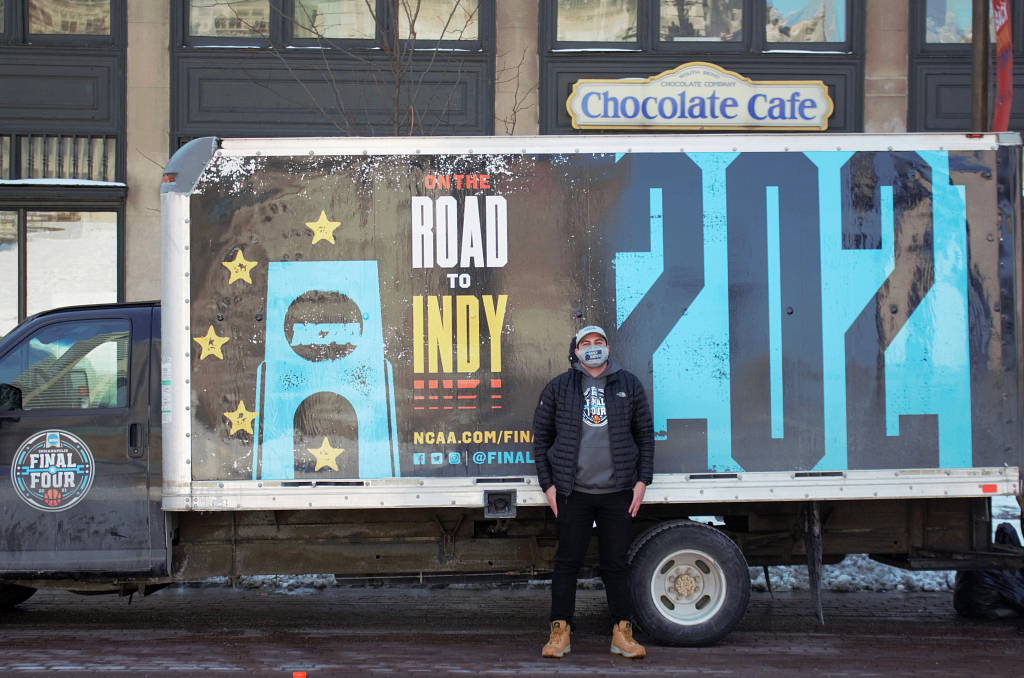 Wally Al-Hamed standing in front of a NCAA branded truck