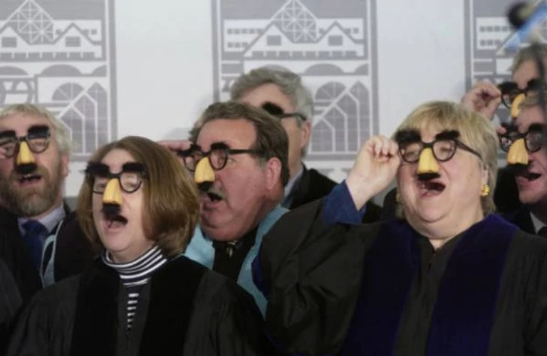 A group of people in black robes wearing fake glasses, noses and mustaches