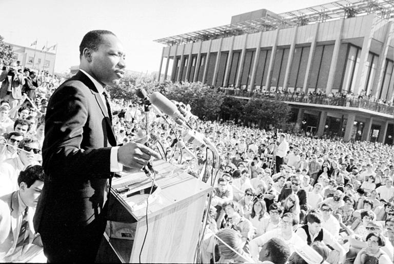 Man addresses crowd from podium